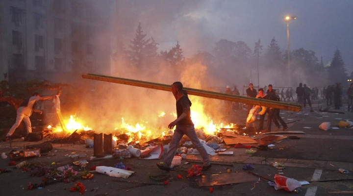 A protester walks past a burning pro-Russian tent camp near the trade union building in Odessa May 2, 2014. At least 38 people were killed in a fire on Friday in the trade union building in the centre of Ukraine's southern port city of Odessa, regional police said. REUTERS/Yevgeny Volokin (UKRAINE - Tags: POLITICS CIVIL UNREST)