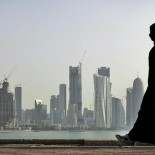 FILE - In this May 14, 2010 file photo, a Qatari woman walks in front of the city skyline in Doha, Qatar. Saudi Arabia and three Arab countries severed ties to Qatar on Monday, June 5, 2017 and moved to cut off land, sea and air routes to the energy-rich nation that is home to a major U.S. military base, accusing it of supporting regional terror groups. (AP Photo/Kamran Jebreili, File)