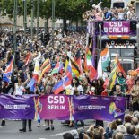 Drag Queens wave different national flags during the Christopher Street Day (CSD) gay pride parade in front of Berlin's Memorial Church (Gedaechtniskirche) in Berlin on June 21, 2014.  AFP PHOTO / CLEMENS BILAN