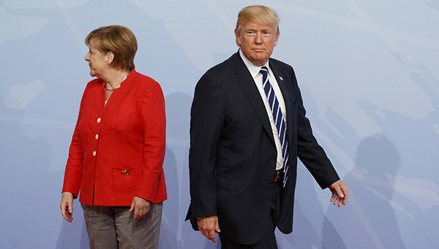 U.S. President Donald Trump walks off after being greeted by German Chancellor Angela Merkel at the G20 Summit, Friday, July 7, 2017, in Hamburg. (AP Photo/Evan Vucci)