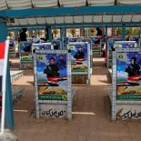 In this Tuesday, April 3, 2018 photo, pictures of Iran-backed paramilitary fighters, most of whom were killed in the war against the Islamic State group, adorn their graves at a cemetery in Najaf, Iraq. Iran's influence is looming large as Iraqis prepare to head to the polls for parliamentary elections in May, with many concerned that Tehran may be looking to strengthen its political grip on Baghdad in the vote. (AP Photo/Khalid Mohammed)