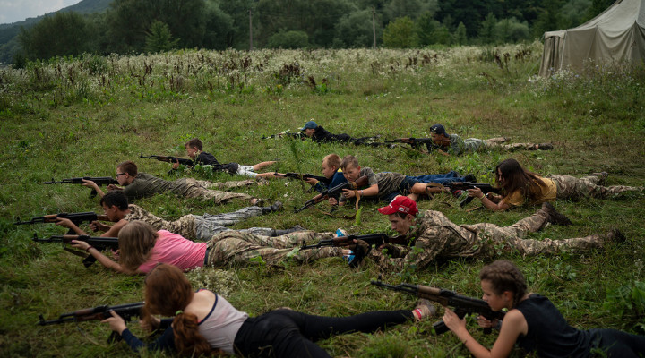 "In this July 28, 2018 photo, young participants of the ""Temper of will"" summer camp, organized by Svoboda party, lay on the ground with their AK-47 riffles during a tactical exercise in a village near Ternopil, Ukraine. (AP Photo/Felipe Dana)"