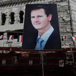 FILE PHOTO: A man walks past a banner depicting Syrian President Bashar al-Assad in Douma, outside Damascus, Syria, September 17, 2018. REUTERS/Marko Djurica/File Photo
