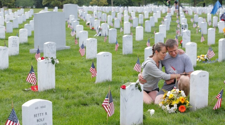 Visitors embrace as they sit next to a grave on Memorial Day at Arlington National Cemetery in Washington, U.S., May 30, 2016. REUTERS/Lucas Jackson