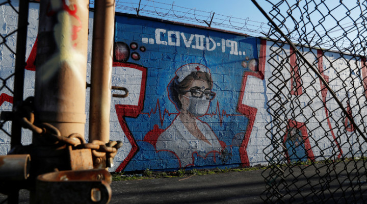 A mural of a female health worker is seen through a fence as the coronavirus disease (COVID-19) continues to spread, in Chicago, Illinois, U.S., April 21, 2020. REUTERS/Shannon Stapleton NO RESALES. NO ARCHIVES.