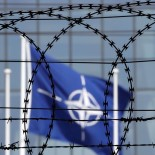 The NATO flag is seen through barbed wire as it flies in front of the new NATO Headquarters in Brussels, Belgium May 24, 2017. Member nations will inaugurate the new NATO headquarters during a summit in Brussels, Belgium May 25, 2017. REUTERS/Christian Hartmann - RC1119E4BBA0