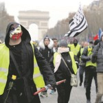 "A protester wearing a yellow vest and an Anonymous mask takes part in a demonstration by the ""yellow vests"" movement in Paris, France, December 15, 2018. REUTERS/Gonzalo Fuentes - RC125E4F7B80"