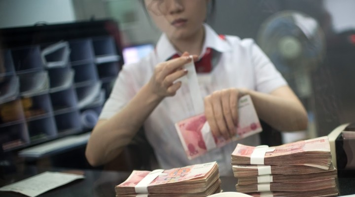 A worker of an Industrial and Commercial Bank of China Ltd (ICBC) branch counts money as she serves a customer in the China (Shanghai) Pilot Free Trade zone during a media trip on September 24, 2014. Concerns over China's economy -- a key driver of global growth -- have intensified following a string of lacklustre recent data, with economists calling for authorities to take further action to kickstart growth. AFP PHOTO / JOHANNES EISELE (Photo credit should read JOHANNES EISELE/AFP/Getty Images)