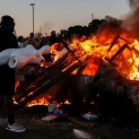A man prepares to throw a mannequin onto a burning car at the parking lot of a Target store during protests after a white police officer was caught on a bystander's video pressing his knee into the neck of African-American man George Floyd, who later died at a hospital, in Minneapolis, Minnesota, U.S., May 28, 2020. REUTERS/Carlos Barria     TPX IMAGES OF THE DAY - RC21YG939C4O